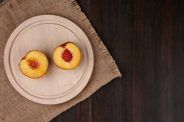 Top view of peaches with apricots and a green apple on a beige napkin on wooden surface