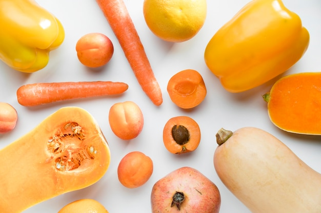 Top view of peaches with carrots and bell pepper
