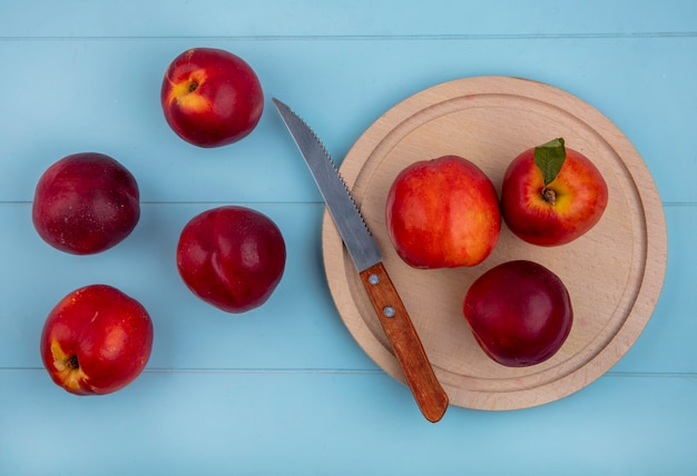 Top view of peaches on a wooden tray with a knife on a light blue surface