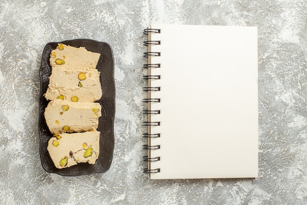 Top view peanut nougat slices inside plate on a white background