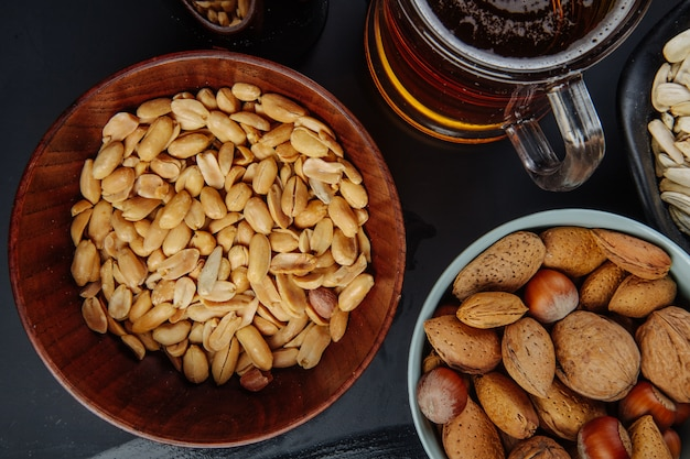 Top view of peanuts in a bowl with almond and a mug of beer on black