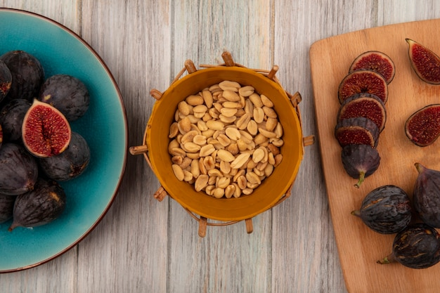 Top view of peanuts on a bucket with black mission figs on a blue bowl with slices of black figs on a wooden kitchen board on a grey wooden wall