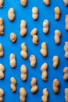 青色の背景にシェルでトップビューピーナッツ