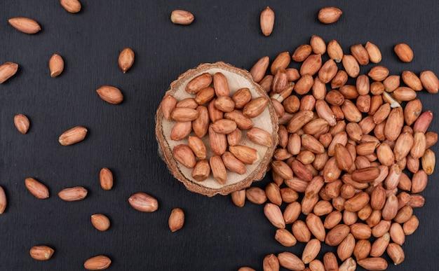 Вид сверху арахис на деревянной подставке в окружении арахиса на темном