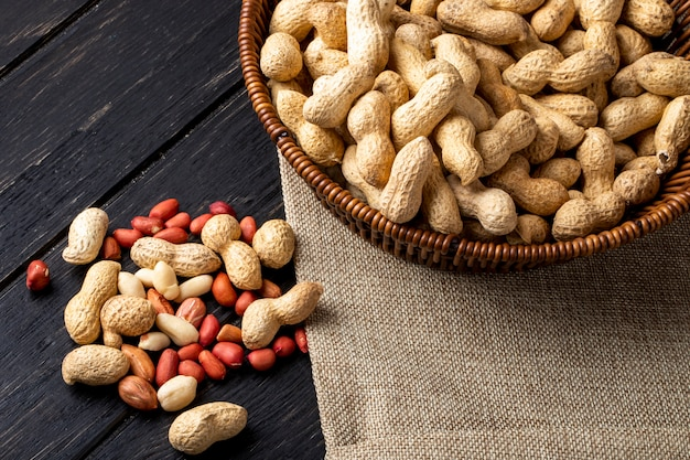 Top view peanuts in shell in a basket with peeled on a black wooden table