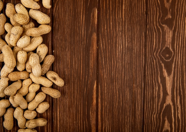 Top view of peanuts in shell scattered on wooden background with copy space