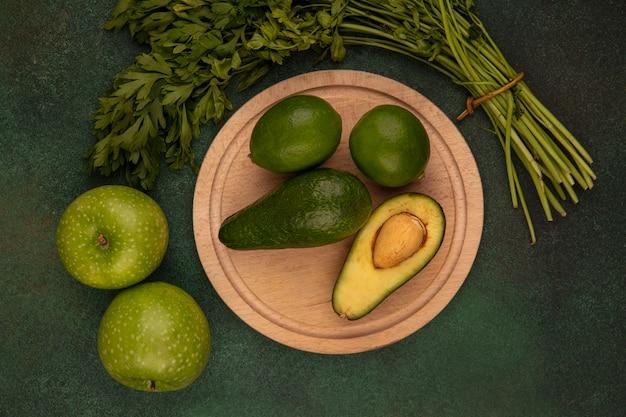 Vista dall'alto di avocado a forma di pera su una tavola di cucina in legno con lime con mele verdi e prezzemolo isolato su uno sfondo verde