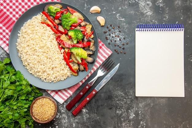 グレーのテーブルオイルライスカラーミール写真健康的な生活の食事療法のおいしい調理された野菜とカトラリーとトップビューパール大麦