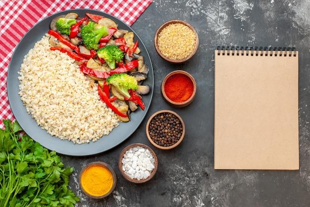 灰色のテーブルにおいしい調理野菜と調味料を添えたトップビューパール大麦