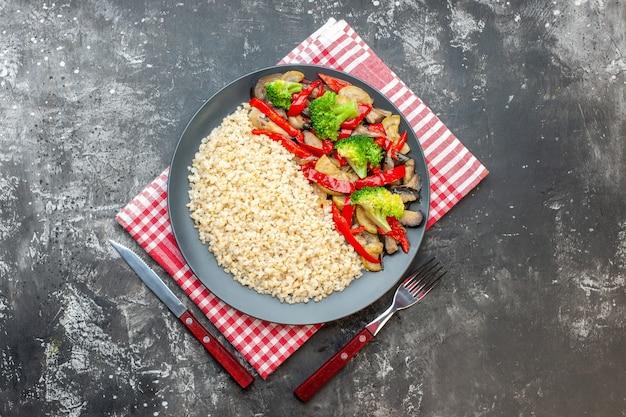 灰色のテーブルの上においしい調理野菜とトップビューパール大麦