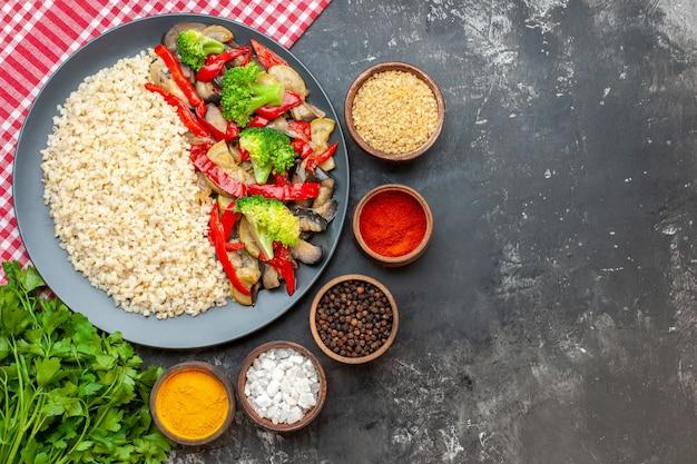 Orzo perlato vista dall'alto con gustose verdure cotte e condimenti sul tavolo grigio