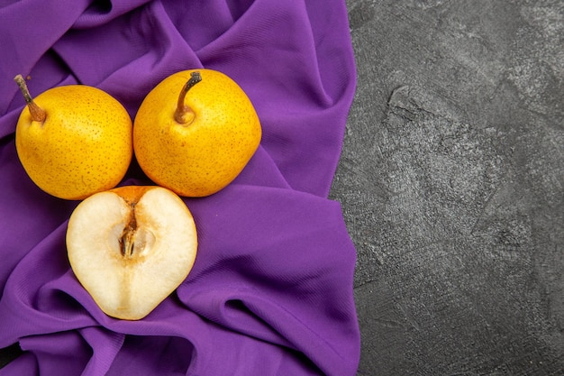 Vista dall'alto pere e mezza pera mezza pera e mezza pera sulla tovaglia sul lato sinistro del tavolo