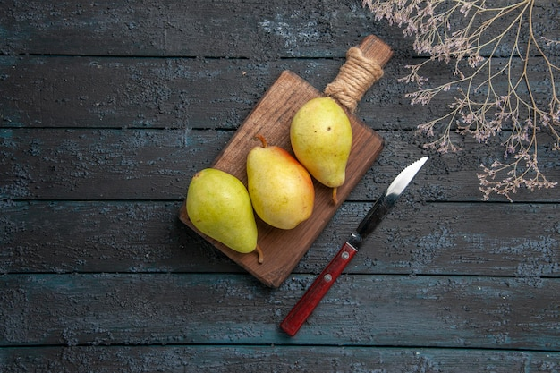 Top view pears and knife three green-yellow-red pears on kitchen board in the center of dark table next to knife and tree branches