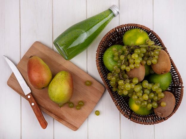 ジュースのボトルとバスケットにみかんとブドウとまな板にナイフでナシの上面図