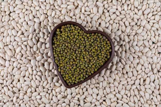 Top view of peas in heart shaped bowl with white beans