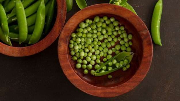 Top view peas in wooden bowl with pods