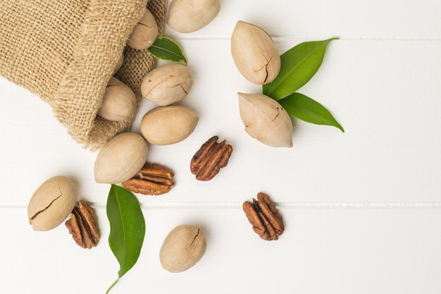 Top view of pecans spilling out of a bag on a white wooden table. vegetarian food.