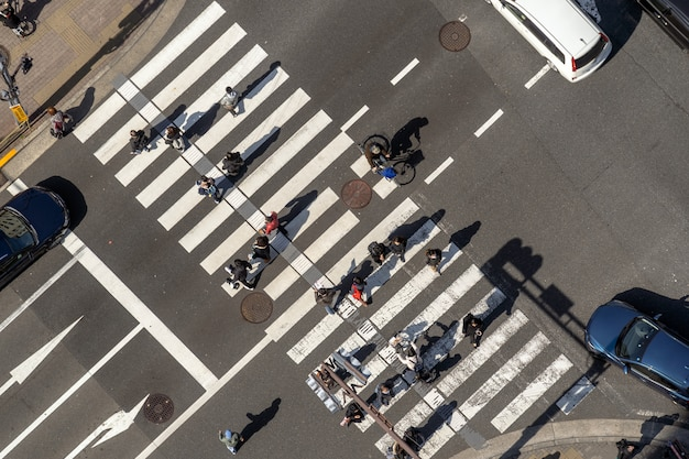 Top view of pedestrians crowd undefined people walking overpass the street intersection cross-walk with sunshine dat in tokyo, japan