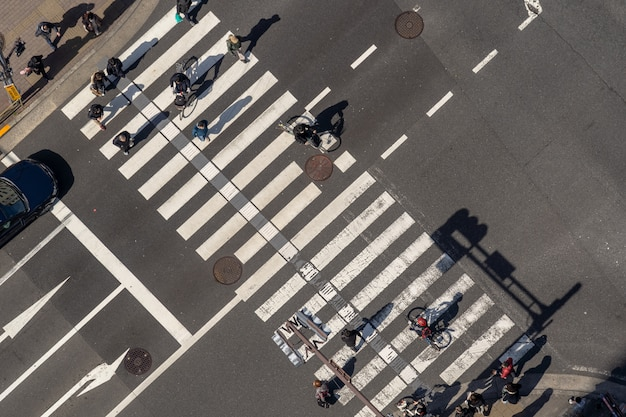 Top view of pedestrians crowd undefined people walking overpass the street intersection cross-walk