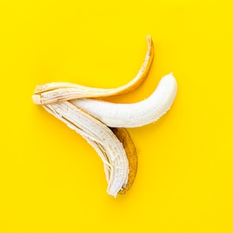 Top view peeled banana on yellow background