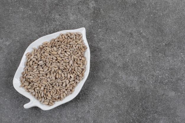 Vista dall'alto di semi di girasole freschi sbucciati sul piatto bianco.