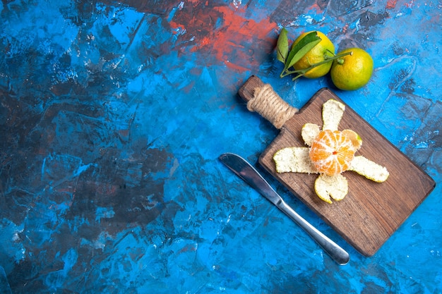 Top view peeled mandarin on chopping board dinner knife fresh mandarines with leaves on blue surface free place