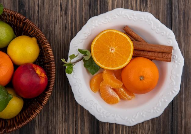 Vista dall'alto spicchi d'arancia sbucciati con cannella in un piatto e limoni lime e pesche in un cesto su sfondo di legno