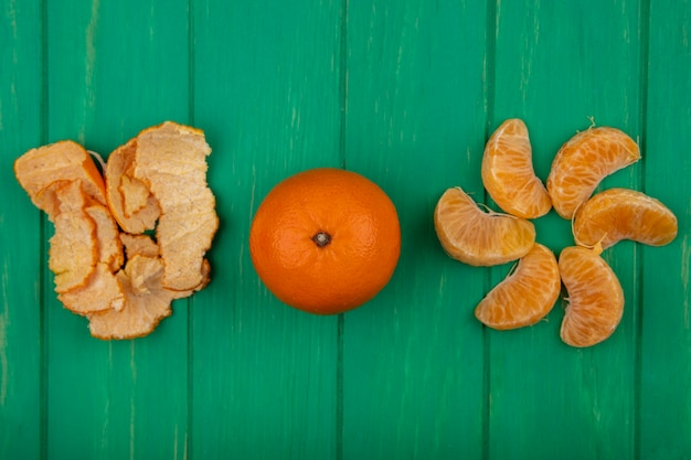 Top view peeled orange wedges with peel on a green background