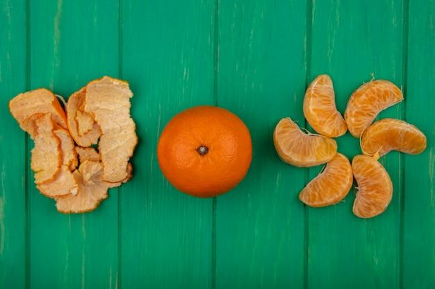 Вид сверху очищенные дольки апельсина с кожурой на зеленом фоне