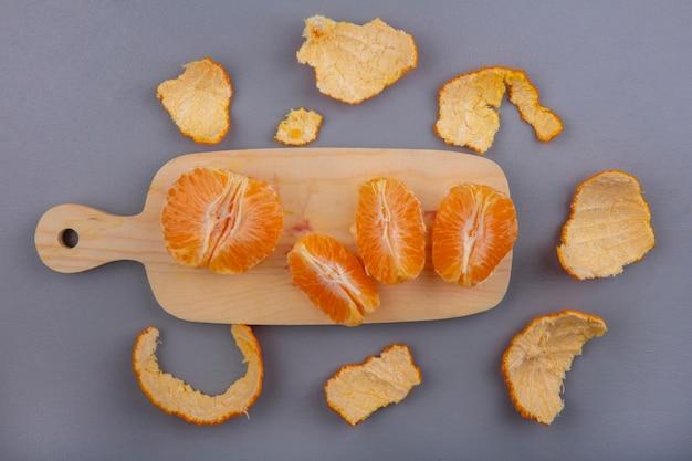 Очищенные апельсины на разделочной доске с кожурой на сером фоне, вид сверху