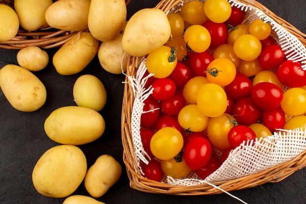 Вид сверху очищенный картофель вместе с желтыми и красными помидорами в корзинах на сером полу