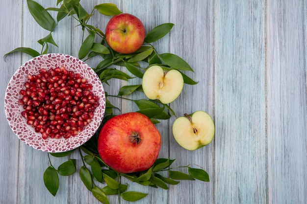 Top view of peeled pomegranate on a plate with halves of a green apple and leaf branches on a gray surface