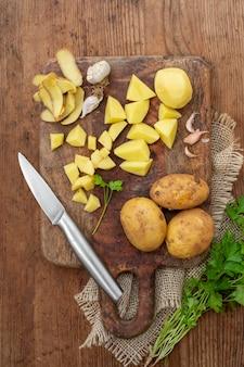 Вид сверху очищенный картофель на деревянной доске