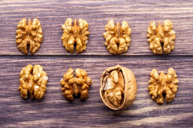 Вид сверху очищенные грецкие орехи с нарезанным орехом на деревянном фоне