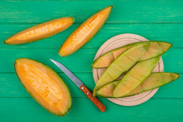 Top view of peels of melon on a wooden kitchen board with knife with slices of melon on green surface