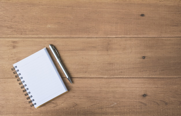 Top view of pen and notebook on wooden background and copy space for insert text.