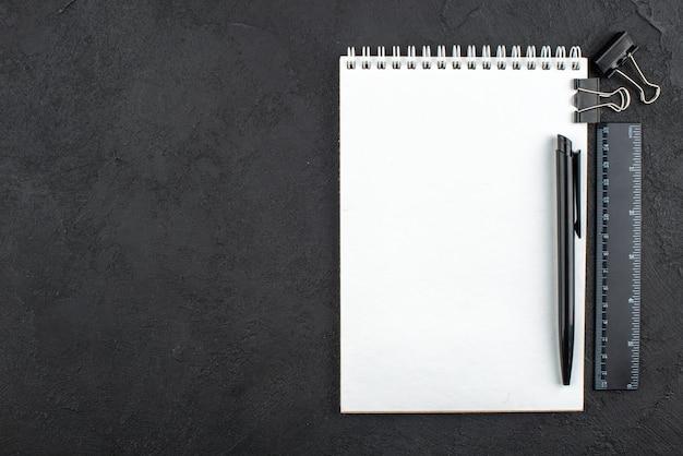 Penna vista dall'alto su clip di rilegatura del righello del blocco note su sfondo scuro