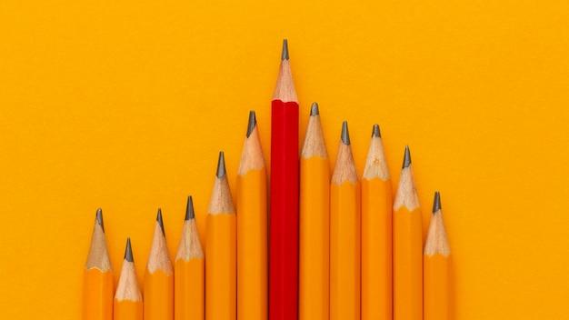 オレンジ色の背景にトップビューの鉛筆