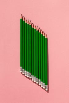 Вид сверху карандаши на розовом фоне