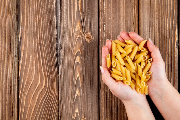 Top view penne pasta on the right with copy space on wooden background