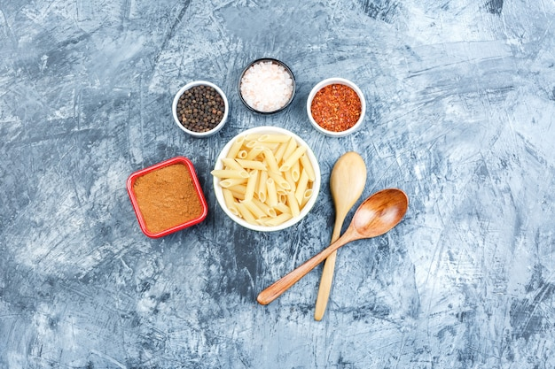 Top view penne pasta in white bowl with wooden spoons, spices on grey plaster background. horizontal