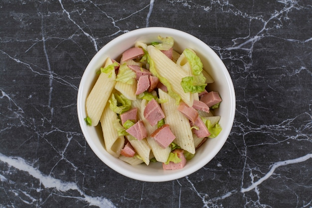 Top view of penne pasta with greens and sausage.