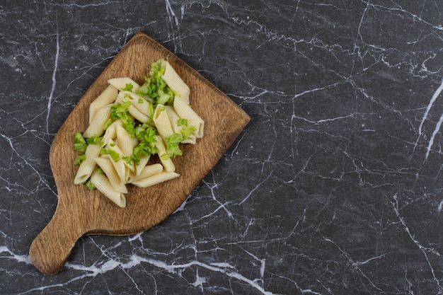 Top view of penne pasta with greens on wooden board over black.