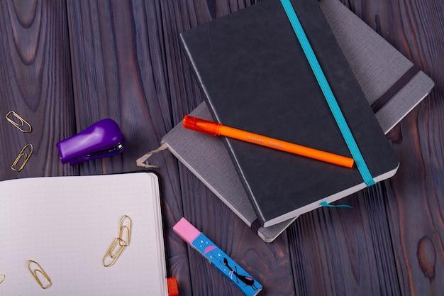 本やペーパークリップ付きのトップビューペン。ダークウッドの背景。