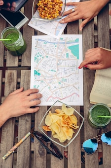 Top view of people hands over map on a wooden table with healthy drinks and snacks. holidays and tourism concept.