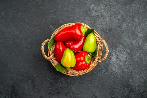 Top view pepper basket with red and green types on dark background with free space