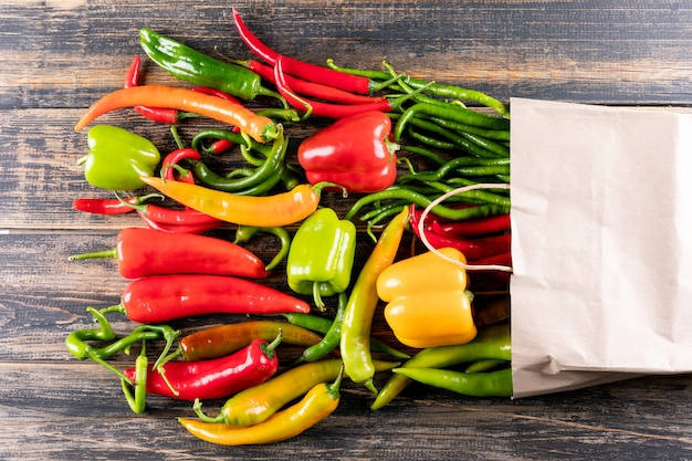 Top view pepper bell pepper and chili with paper bag on brown wooden  horizontal