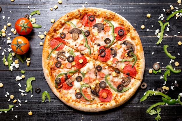 Top view of pepperoni pizza with mushroom sausages bell pepper olive and corn on black wooden