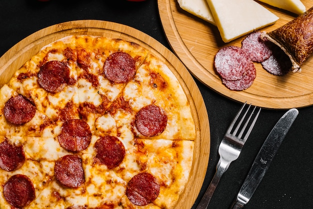Top view of pepperoni pizza with tomato sauce and cheese