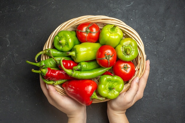 Vista dall'alto peperoni e pomodori nella ciotola del cesto di vimini in mano femminile sulla superficie scura